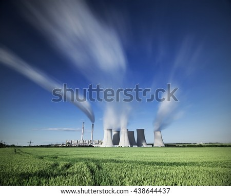 A coal-fired power station in the distance in agricultural landscape. long time, Pocerady, Czech republic - stock photo
