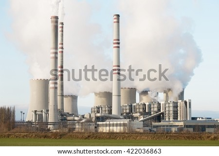 A coal-fired power station in the distance in agricultural landscape. Pocerady, Czech republic - stock photo
