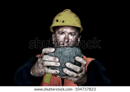 A coalminer holds out a large chunk of energy rich coal in a dark coalmine. - stock photo