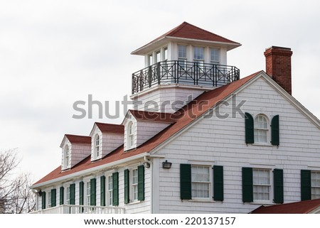 A coastal home with red roof and green shutters, dormers and a widows walk - stock photo