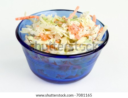A cobalt blue bowl of fresh coleslaw. - stock photo