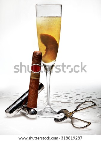 a cocktail with beautiful garnish, a cigar and a cut cigar machine with drops on background - stock photo