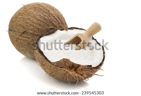 A coconut with desiccated coconut and scoop on white background - stock photo