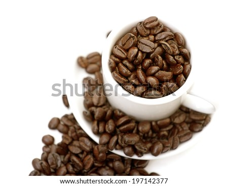 A coffee cup and saucer are overflowing with coffee beans. - stock photo