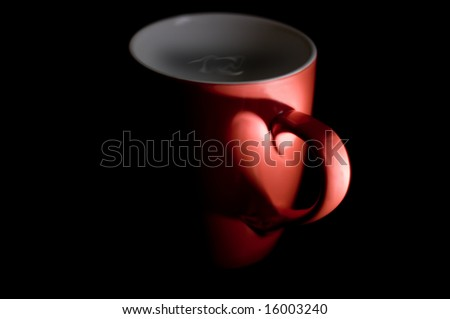 a coffee mug in the shadows with a heart shape formed by the shadows - stock photo