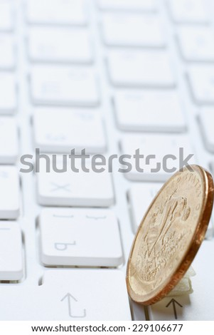 A coin on a laptop keyboard - stock photo