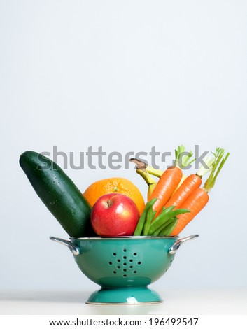 A colander holding beans, carrots, a cucumber, apple, orange and bananas. - stock photo