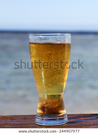 A Cold icy beer on a bar with the tropical ocean and blue sky in the background. - stock photo