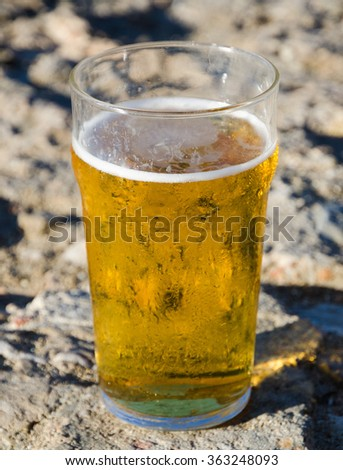 A cold pint of refreshing beer in a sunny hot environment - stock photo