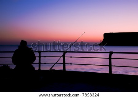 A cold still winters morn sees a lone fisherman patiently awaiting a bite - stock photo