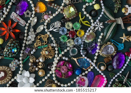 A collage of plastic trinkets and gaudy costume jewelry makes a colorful homage to kitsch. - stock photo
