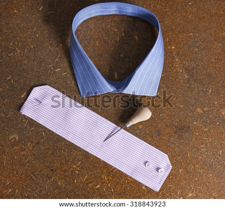 a collar,a sleeve with a sewing tool on a plan - stock photo