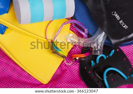 A collection of competitive swimming equipment or gear for swim team spilling out on ground.  Including goggles, fins, and kick board on a pink net swim bag - stock photo