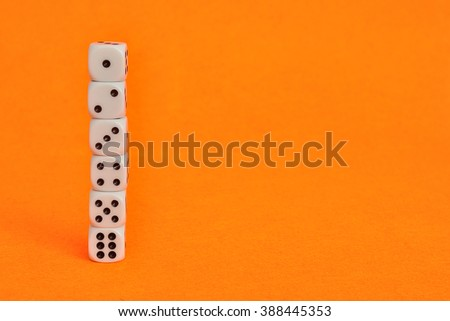 A collection of dices that is displayed on an orange background - stock photo