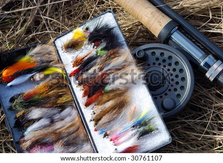 A collection of fly fishing flies and fly fishing rod - stock photo