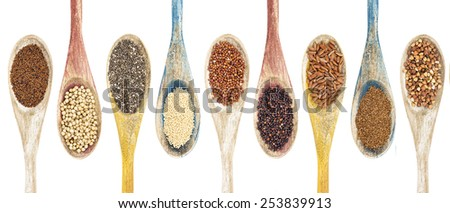 a collection of gluten free grains and seeds on isolated wooden spoons - kaniwa, sorghum, chia, amaranth,red quinoa, black quinoa, brown rice, teff, buckwheat  (from left to right) - stock photo
