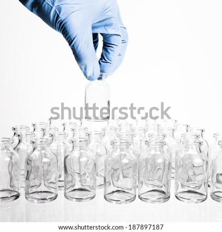 A collection of many small empty scientific vials in rows with a hamd wearing a blue latex glove holds one container up. - stock photo