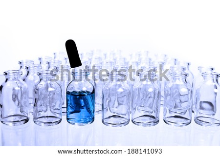 A collection of many small empty scientific vials in rows with a single eye-dropper in one of the containers that has a blue liquid in it,  tinted with a cool blue filter. - stock photo
