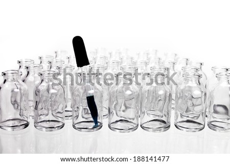 A collection of many small empty scientific vials in rows with a single eye-dropper in one of the containers. - stock photo