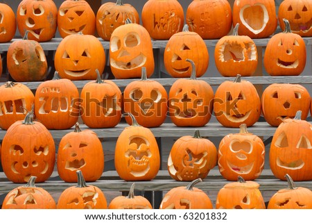 A collection of pumpkins with various different designs cut into them. - stock photo