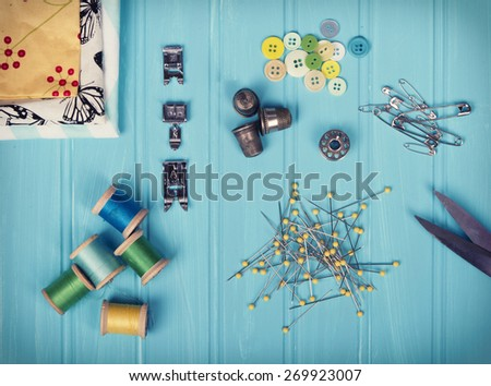 A collection of sewing items including: thread, thimbles, pins, buttons, bobbin, sewing machine feet and material on a turquoise background - stock photo