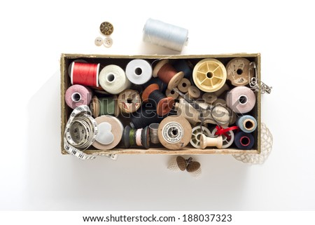 a collection of thread spools in a wooden box on white background with accessories - stock photo