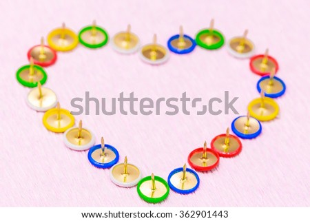 A collection of thumbtacks arranged in heart shape. Close-up on pink background. - stock photo