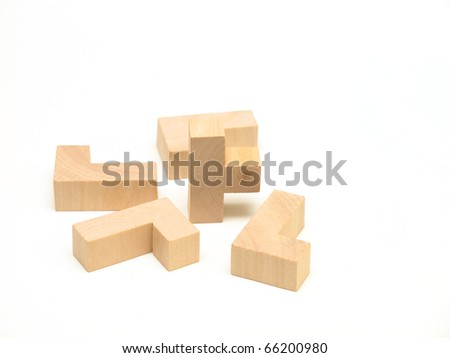 A collection of wooden puzzle elements on white surface. - stock photo