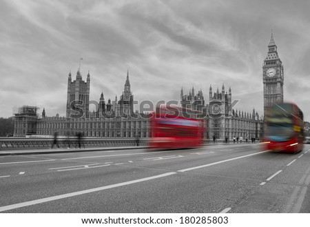 A color mix of Westminster showing bright red buses on a black and white image of Westminster. - stock photo