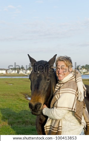 A color portrait photo of a handsome blonde man in his forties petting his brown horse. - stock photo