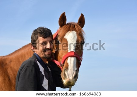 A color portrait photo of a handsome smiling man petting his beautiful horse - stock photo