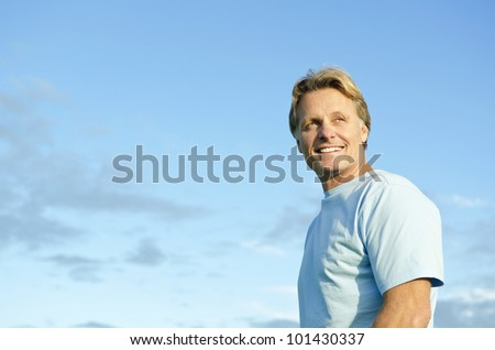 A color portrait photo of a happy smiling blond haired man in his forties wearing a blue t'shirt against a blue sky backround. - stock photo