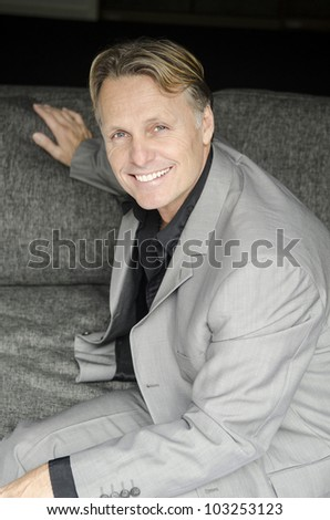 A color portrait photo of a happy smiling mature man in his forties sitting on a sofa and looking at the camera. - stock photo