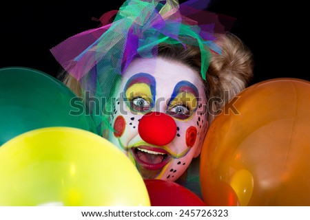 A colored clown face looks between colorful balloons in to the camera - stock photo