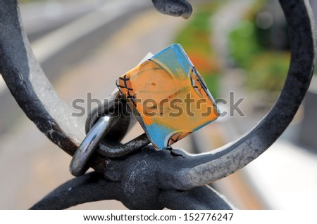 A Colored Metal Lover's Lock on a Bridge - stock photo