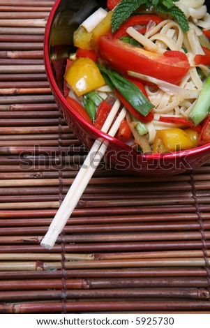 A colorful asian dish of noodles over a bamboo placemat - stock photo