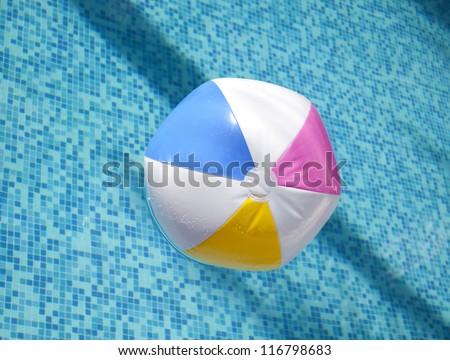 A colorful ball floating in a blue swimming pool. - stock photo