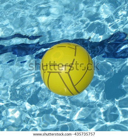 A colorful ball floating in a blue swimming pool - stock photo