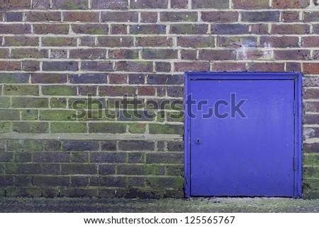 A colorful brick wall with a small blue door in it - stock photo
