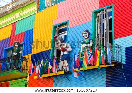 A colorful building in La Boca neighborhood of Buenos Aires with statues and flags - stock photo