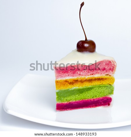 A colorful cake decorated with a cherry on the top  - stock photo