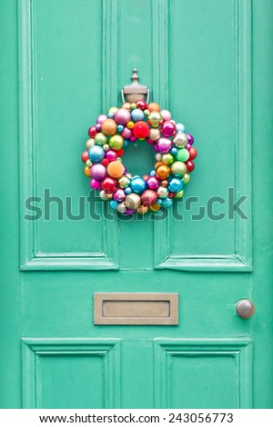 A colorful christmas wreath on a green front door - stock photo