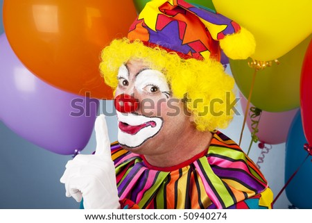A colorful clown putting his finger to his lips so you will be quiet. - stock photo