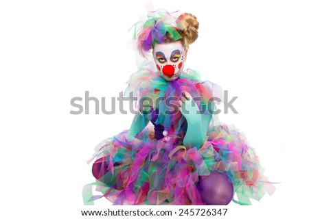 A colorful clown sitting cross-legged, looking sadly into the camera - stock photo
