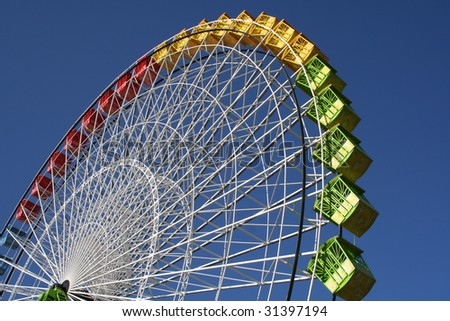 A colorful ferris wheel against blue sky. - stock photo