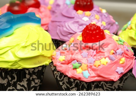 A colorful homebaked batch of cupcakes with their feminine touches. - stock photo