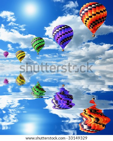 A colorful hot air balloon floating over water in a beautiful sky - stock photo