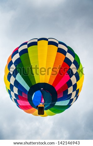 A colorful hot air balloon rises above - stock photo
