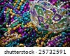 A colorful mardi gras crown or tiara lying on top of beads, holiday theme - stock photo
