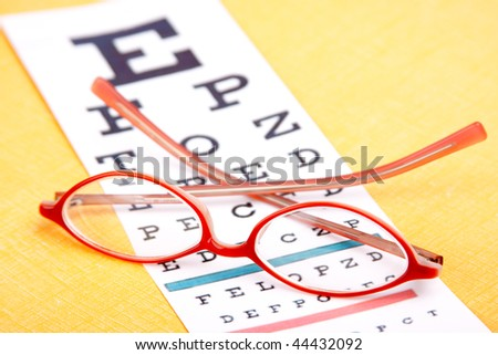A colorful pair of eyeglasses rest on an eye chart. Bright yellow background. Shallow dof. - stock photo